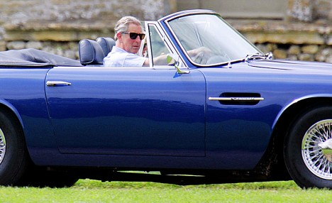 Prince Charles driving his Aston Martin arrives at Cirencester Polo Ground with Camilla, Duchess of Cornwall.